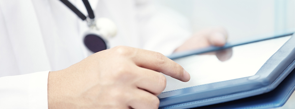 doctor with stethoscope using an ipad