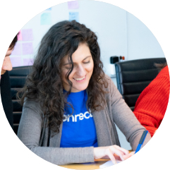 A woman with curly hair and a blue connected t-shirt taking notes