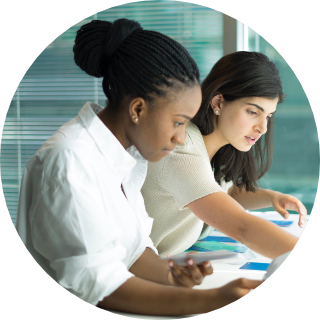 Two women working with playbook cards