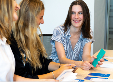 Three smiling women sitting at a table discussing Playbook cards.