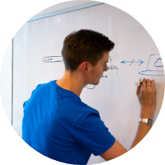 A man in a blue shirt writing on a whiteboard